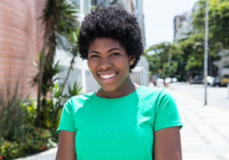 Laughing african woman in a green shirt in the city Stock Photo