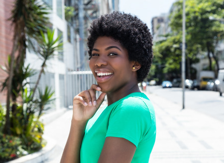 Happy african woman in a green shirt in the city