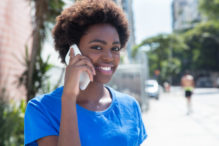 Laughing african american woman in a blue shirt at phone Stock Photo