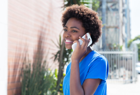 African american woman in a blue shirt speaking at phone