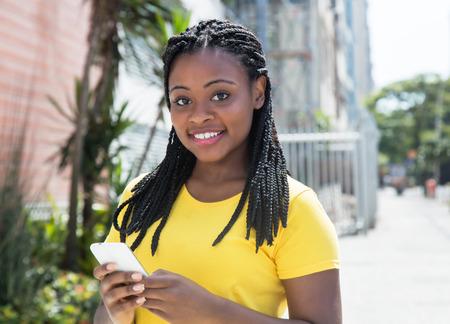 mujer afroamericana en un mensaje escribiendo la camisa amarilla con el teléfono móvil