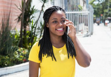 Gelukkig Afro-Amerikaanse vrouw in een geel shirt op de mobiele telefoon