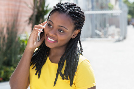 Laughing african american woman in a yellow shirt at mobile phone