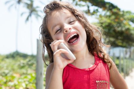 niños riendose: El niño feliz en una camisa roja se ríen del teléfono móvil fuera Foto de archivo