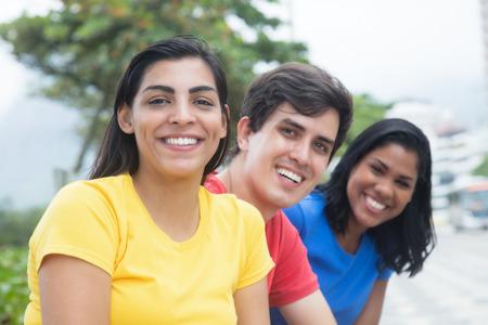 Mooie Latijnse vrouw in een geel shirt met vrienden