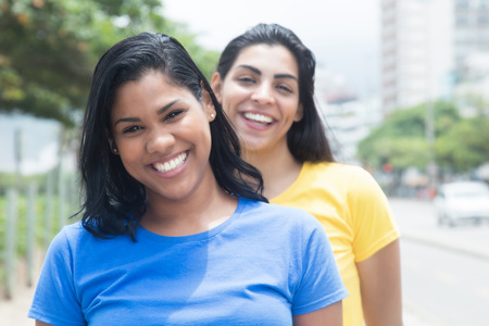 Two mexican girlfriends in colorful shirts in the city Foto de archivo