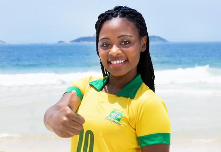 brazilian woman: Brazilian woman in a soccer jersey at beach showing thumb