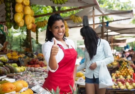 Lachen Mexicaanse verkoopster toont duim op een boerenmarkt