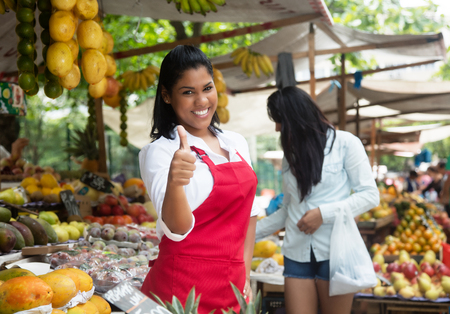 Laughing mexican saleswoman showing thumb on a farmers market