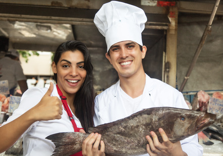 colombian food: Chef and clerk with fresh fish on a market