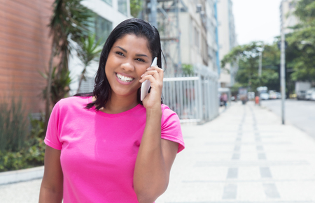 sexy woman standing: Native american woman laughing at phone in the city Stock Photo