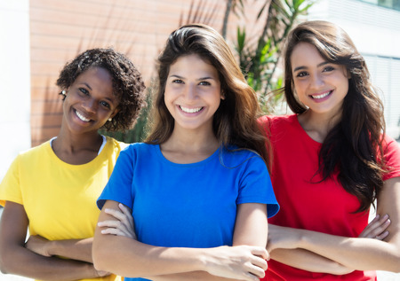 Three happy girlfriends in colorful shirts