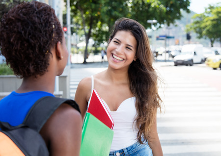 african student: Beautiful caucasian student speaking with african american girlfriend Stock Photo