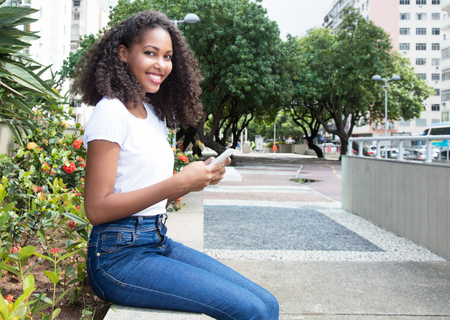 message sending: Latin woman with curly hair sending message with phone