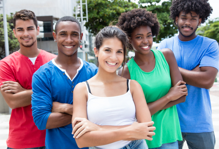 Group of multi ethnic young adults with crossed arms in city