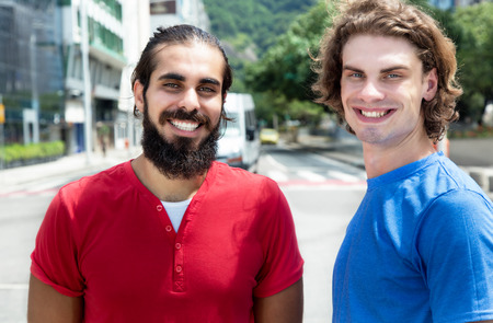 european integration: Modern caucasian guy with arabian friend