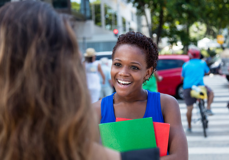 african student: African american female student meets a caucasian girlfriend Stock Photo