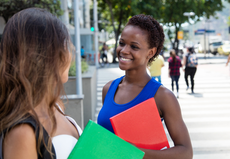 african student: African american female student talking to caucasian girlfriend