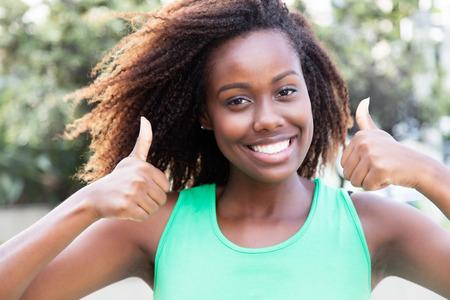 Donna dell'afroamericano in una camicia verde che mostra entrambi i pollici