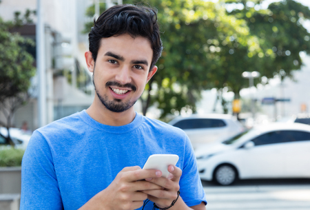 message sending: Happy hispanic guy sending message with phone