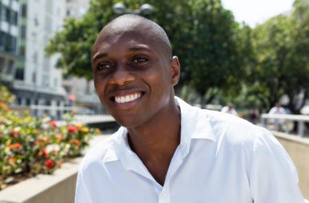 afroamericanas: Atractivo hombre afroamericano en la camisa blanca al aire libre Foto de archivo