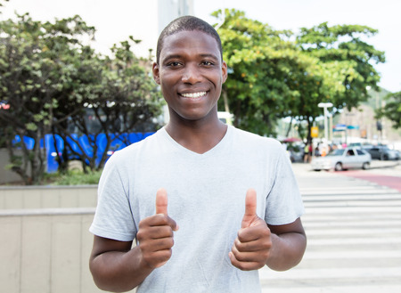 adult kenya: African american guy showing both thumbs outdoor Stock Photo