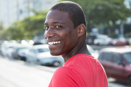 adult kenya: African american guy in a red shirt looking back