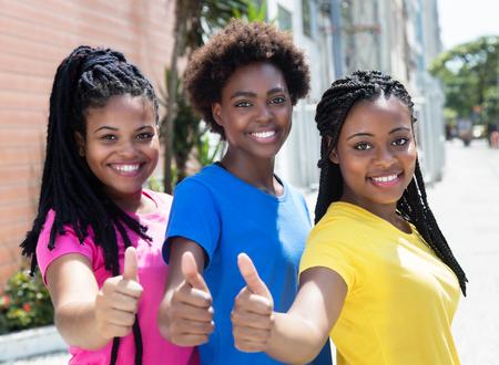 Drie lachende Afro-Amerikaanse vriendinnen zien thumbs up