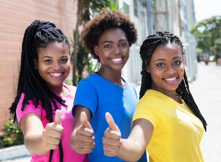 Three laughing african american girlfriends showing thumbs up
