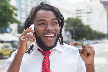 rastas: hombre de negocios feliz del afroamericano con los dreadlocks en el tel�fono