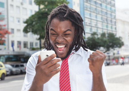 online bidding: Cheering african american businessman with dreadlocks and phone