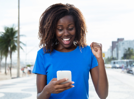 bidding: Cheering african woman in a blue shirt with phone