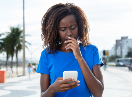 Thinking african woman in a blue shirt with phone