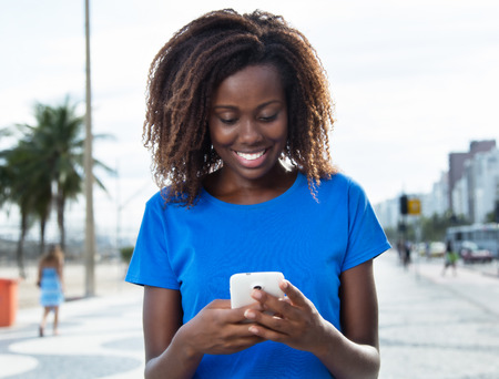 Laughing african woman in a blue shirt sending message with phone 免版税图像