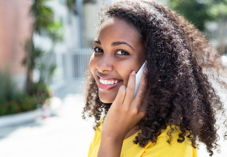 Smiling latin woman with curly hair at phone in summer