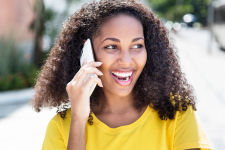 Laughing latin woman with curly hair at phone in summer