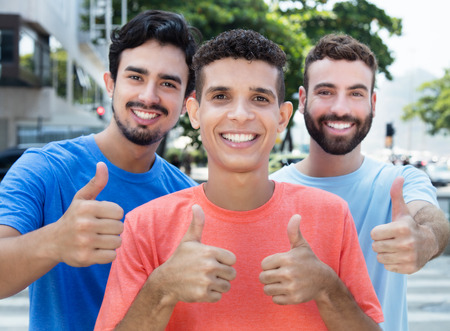 Three latin and caucasian friends showing thumb up Stock Photo