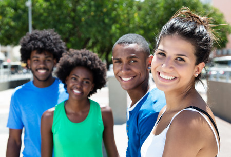 Beautiful young caucasian woman with african american friends in the city Stockfoto