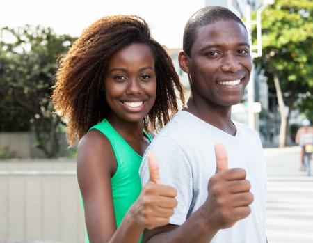Mooie African American paar dat duim toont in de stad Stockfoto