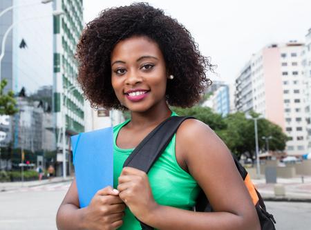 Felice studentessa dall'Africa in camicia verde in città