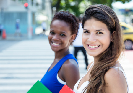 african student: Happy caucasian female student with african american girlfriend Stock Photo