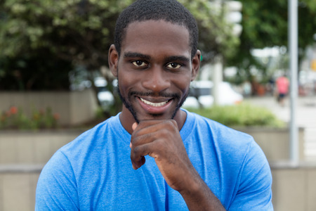 African american man with blue shirt looking at camera