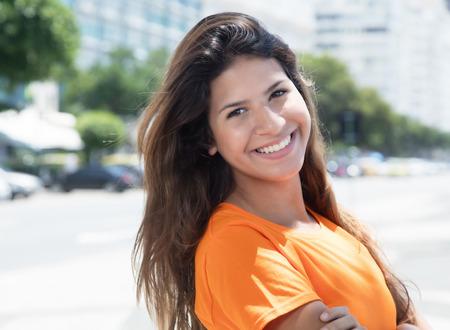 Cute caucasian woman in a orange shirt in the city Stock Photo