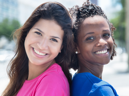 latina america: African american and caucasian girlfriend back to back Stock Photo