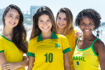 Group of laughing brazilian soccer fans outdoor in the city in the summer