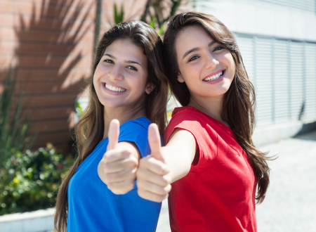 latina america: Two caucasian girlfriends showing thumb outdoor in the city in the summer Stock Photo
