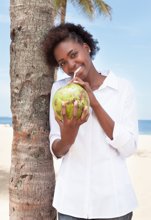 african american woman: Happy african american woman drinking coconut water