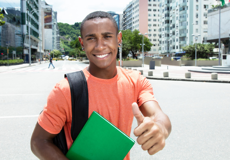 african student: African american male student showing thumb in city