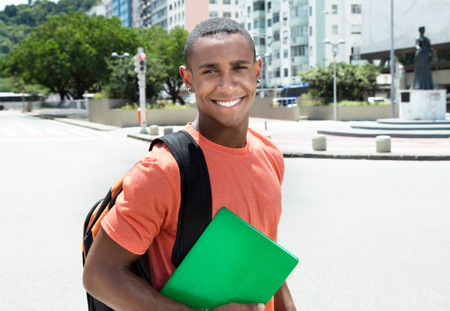 african student: Laughing african american male student in city