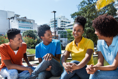 Group of four speaking latin american young adult outdoor